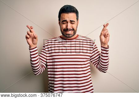 Young handsome man with beard wearing casual striped t-shirt standing over white background gesturing finger crossed smiling with hope and eyes closed. Luck and superstitious concept.