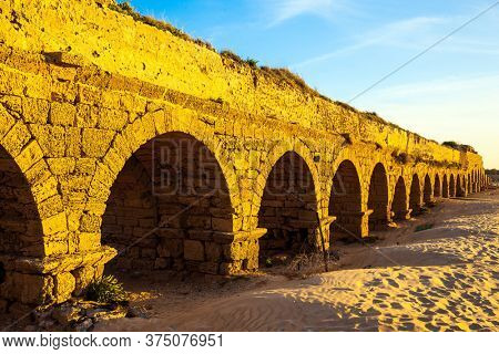 Magical sunset in Caesarea on the shores of the Mediterranean Sea. The ancient Roman aqueduct is lit by the setting sun. Long evening shadows lie evenly on the warm sand. Summer in Israel.
