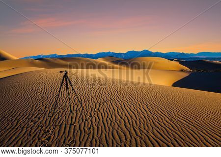 Photographic tripod prepared for evening shooting. USA. Mesquite Flat Sand Dunes, Death Valley, California. Light sand waves from the desert wind. Woman with a camera and a tripod goes among the dunes