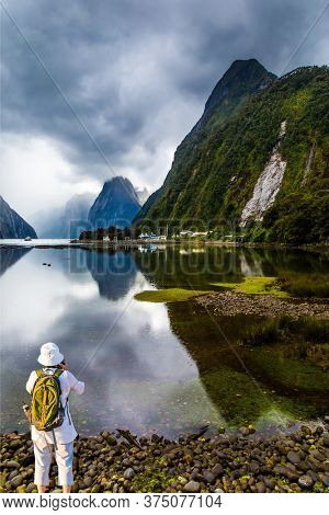 Woman with backpack in white hat photographs picturesque landscape. New Zealand. Mirror-smooth water of the Milford Sound fjord reflects mountains. Concept of exotic, active and photographic tourism