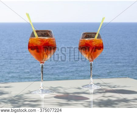 Close Up Of Two Glasses Of Chilled Cocktail Drinks With Straws And  Ice Cubes On A Table A Sunny Day