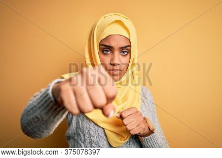 Young beautiful african american girl wearing muslim hijab over isolated yellow background Punching fist to fight, aggressive and angry attack, threat and violence