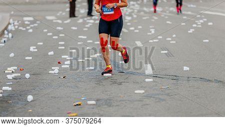 Legs Girl Runner Run On Asphalt Near Water Point On Plastic Cups And Refreshing Sponges