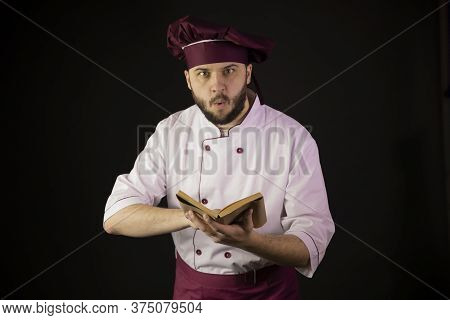 Shocked Chef Man In Uniform Holds Cook Book Recipe-book Looks At Camera With Surprise. Cook In Apron