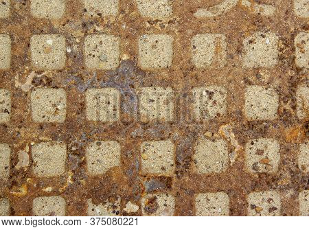 Rusty Sewer Manhole Cover. Geometric Pattern On The Cover Of The Sewer Manhole. The Dents In The Sew