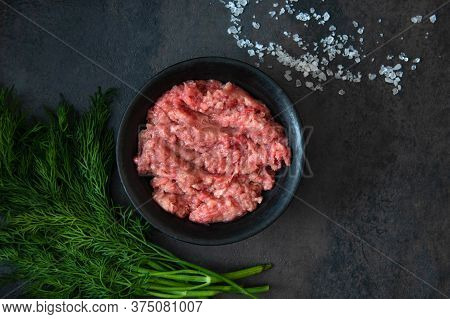 Homemade Minced Meat In A Black Bowl With Ingredients. Fresh Raw Mince. Top View With Copy Space