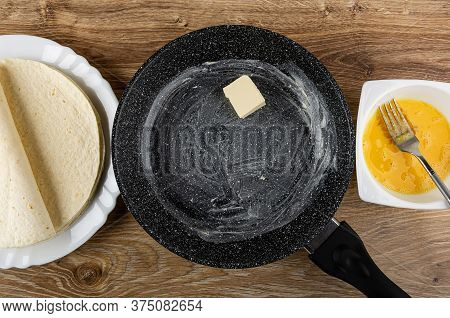 Few Wheat Tortilla In White Dish, Frying Pan Greased Butter, Fork In White Bowl With Mixed Raw Eggs