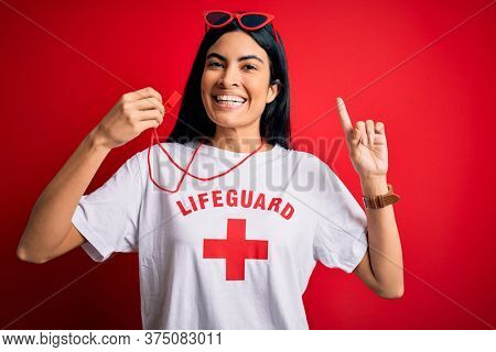 Young beautiful hispanic lifeguard woman wearing safeguard t-shirt holding whistle surprised with an idea or question pointing finger with happy face, number one