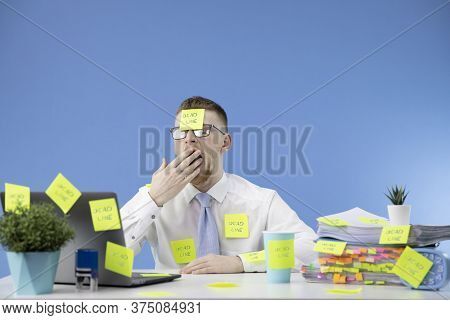 Deadline Concept. Overworked Young Businessman In Glass And Tie Yawning With Notes All Around His Of