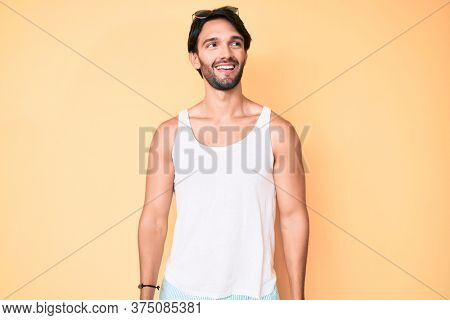 Handsome hispanic man wearing summer look and sunglasses smiling looking to the side and staring away thinking.