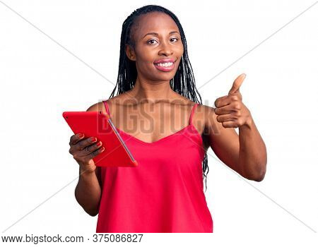 Young african american woman holding touchpad smiling happy and positive, thumb up doing excellent and approval sign