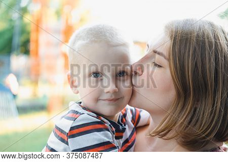 Mother Hugs And Kissing Her Baby Boy On The Park. Motherhood - Young Mother Hugging Her Happy Baby O