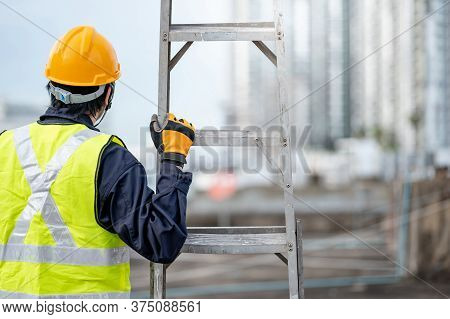 Asian Maintenance Worker Man With Safety Helmet And Green Vest Carrying Aluminium Step Ladder At Con