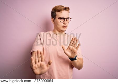 Young handsome redhead man wearing casual t-shirt standing over isolated pink background Moving away hands palms showing refusal and denial with afraid and disgusting expression. Stop and forbidden.