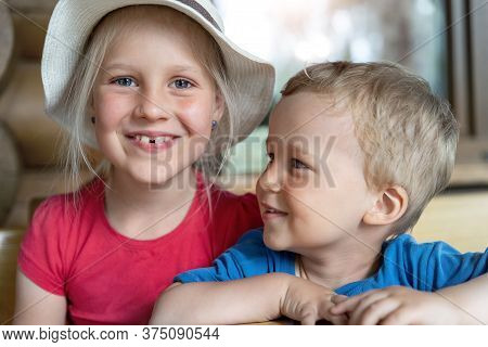 Two Cute Adorable Caucasian Blond Little Siblings Sitting At Table Home Yard And Having Fun Play Tog