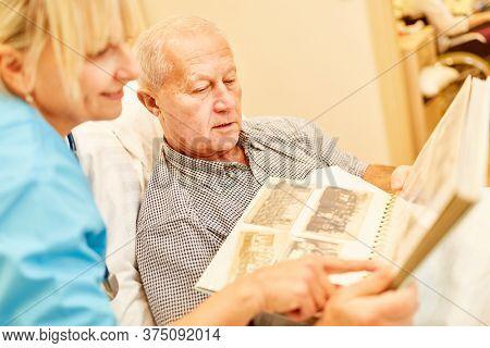 Senior man with dementia looks at a photo album together with geriatric nurse