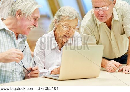 Senior group at laptop computer is having fun with social media and internet