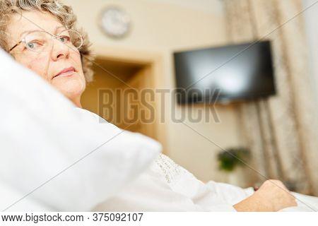 Sick senior is lying in bed in nursing home or senior citizen apartment