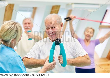Vital senior man doing fitness training in a physiotherapy course