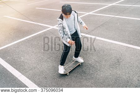 Teenager Skateboarder Boy With A Skateboard On Asphalt Playground Doing Tricks. Youth Generation Fre
