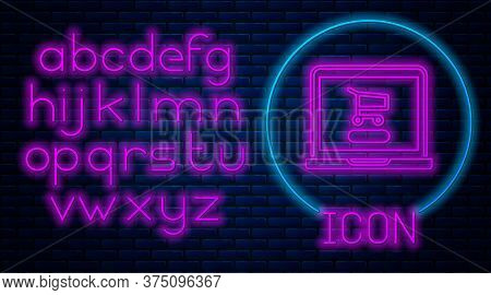Glowing Neon Shopping Cart On Screen Laptop Icon Isolated On Brick Wall Background. Concept E-commer