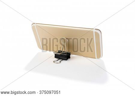 Lifehack; binder clip as a smart phone stand isolated on white background