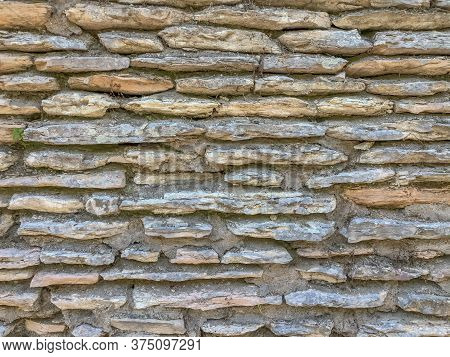 Old Textured Stone Wall Background Close-up. Copy Space. Brown, Gray, Blue Stones