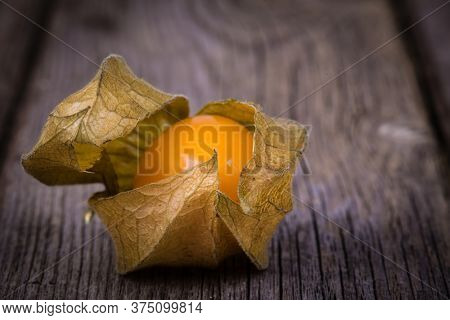Physalis, or Cape Gooseberry fruit over old wood background. Vintage effect with intentional vignette