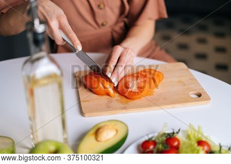 Close-up Of Hand Of Woman Cutting Fresh Tomato Using Kitchen Knife On Wooden Cutting Board. Young Wo