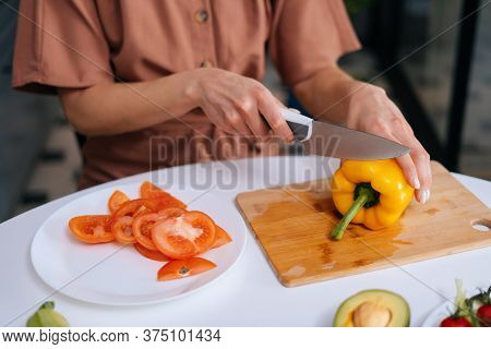 Close-up Of Hand Of Woman Cutting Fresh Bell Pepper Using Knife On Wooden Cutting Board. Young Woman