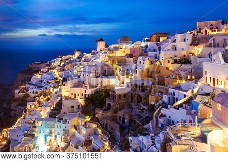 Oia On Sunset. Oia Or Ia Is A Small Town In The South Aegean On The Islands Of Santorini In The Cycl