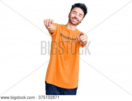 Young hispanic man wearing t shirt with happiness word message pointing to you and the camera with fingers, smiling positive and cheerful