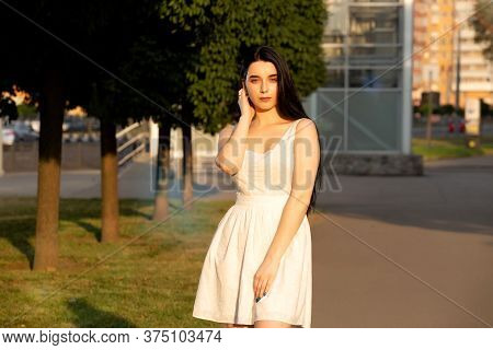 Portrait Of A Beautiful Young Smiling Brunette Outdoors With Natural Sunset Light From The Sun. Clos