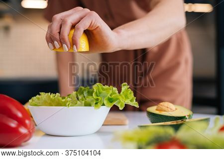 Close-up Of Womens Hands Squeezing Juice From Fresh Yellow Lemon Into Salad Bowl With Sliced Vegetab