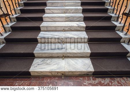 Old Marble Stairs With Dark Brown Carpet