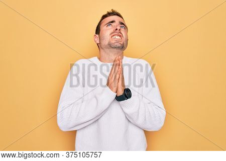 Young handsome man with blue eyes wearing casual sweater standing over yellow background begging and praying with hands together with hope expression on face very emotional and worried. Begging.