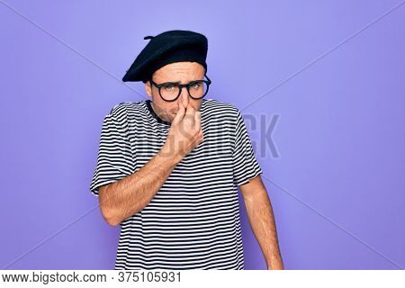 Handsome man with blue eyes wearing striped t-shirt and french beret over purple background smelling something stinky and disgusting, intolerable smell, holding breath with fingers on nose. Bad smell