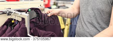 Close-up Of Person In Shopping Centre. Man Choosing Outerwear In Store. Stylish And Comfy Jackets On