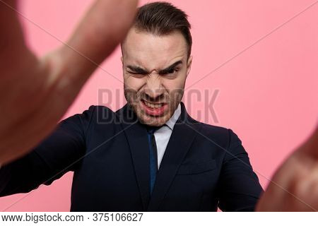 young elegant businessman in suit making silly faces, holding and framing the camera, standing on pink background
