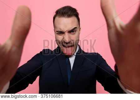 funny young elegant man sticking out tongue and making silly faces, framing and holding the camera, standing on pink background