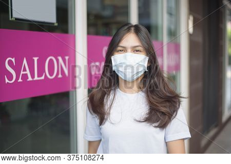 A Young Woman Is Getting A Haircut In A Hair Salon , Wearing Face Mask For Protection Covid-19 , Sal