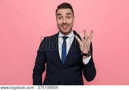 enthusiastic elegant man holding fingers up and gesturing, smiling and standing on pink background