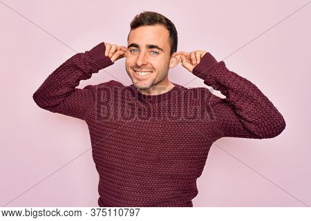 Young handsome man with blue eyes wearing casual sweater standing over pink background Smiling pulling ears with fingers, funny gesture. Audition problem