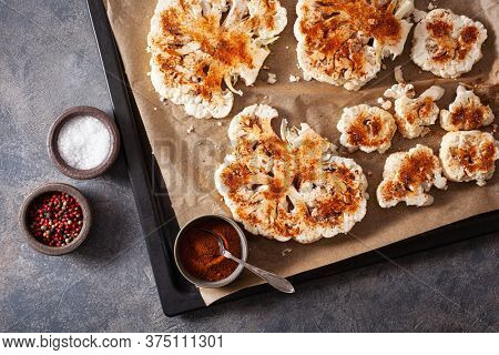 raw cauliflower steaks with spice on baking tray. plant based meat substitute