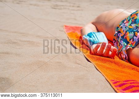 closeup of a caucasian man, lying face down on a colorful orange towel on the beach, wearing a blue surgical mask in his arm, as is taking a breather of wearing it