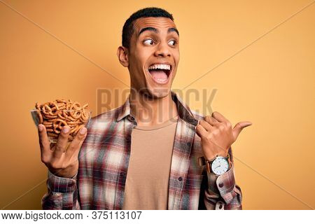 Young handsome african american man holding bowl with german baked pretzels pointing and showing with thumb up to the side with happy face smiling