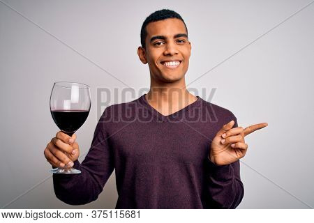 Handsome african american sommelier man tasting glass of red wine over white background very happy pointing with hand and finger to the side