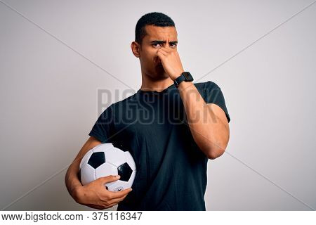 Handsome african american man playing footbal holding soccer ball over white background smelling something stinky and disgusting, intolerable smell, holding breath with fingers on nose. Bad smell