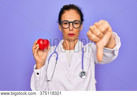 Middle age senior cardiologist doctor woman holding red heart over purple background with angry face, negative sign showing dislike with thumbs down, rejection concept