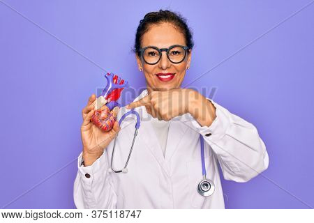 Middle age senior cardiologist doctor woman holding professional cardiology heart very happy pointing with hand and finger